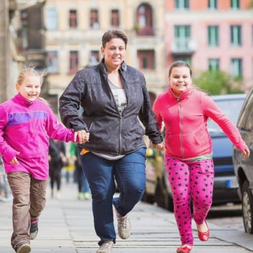 Eine Mutter mit zwei Töchtern, die fröhlich die Straße entlang gehen. Wir stärken Familien und machen ihnen Mut. Stoffwechsel