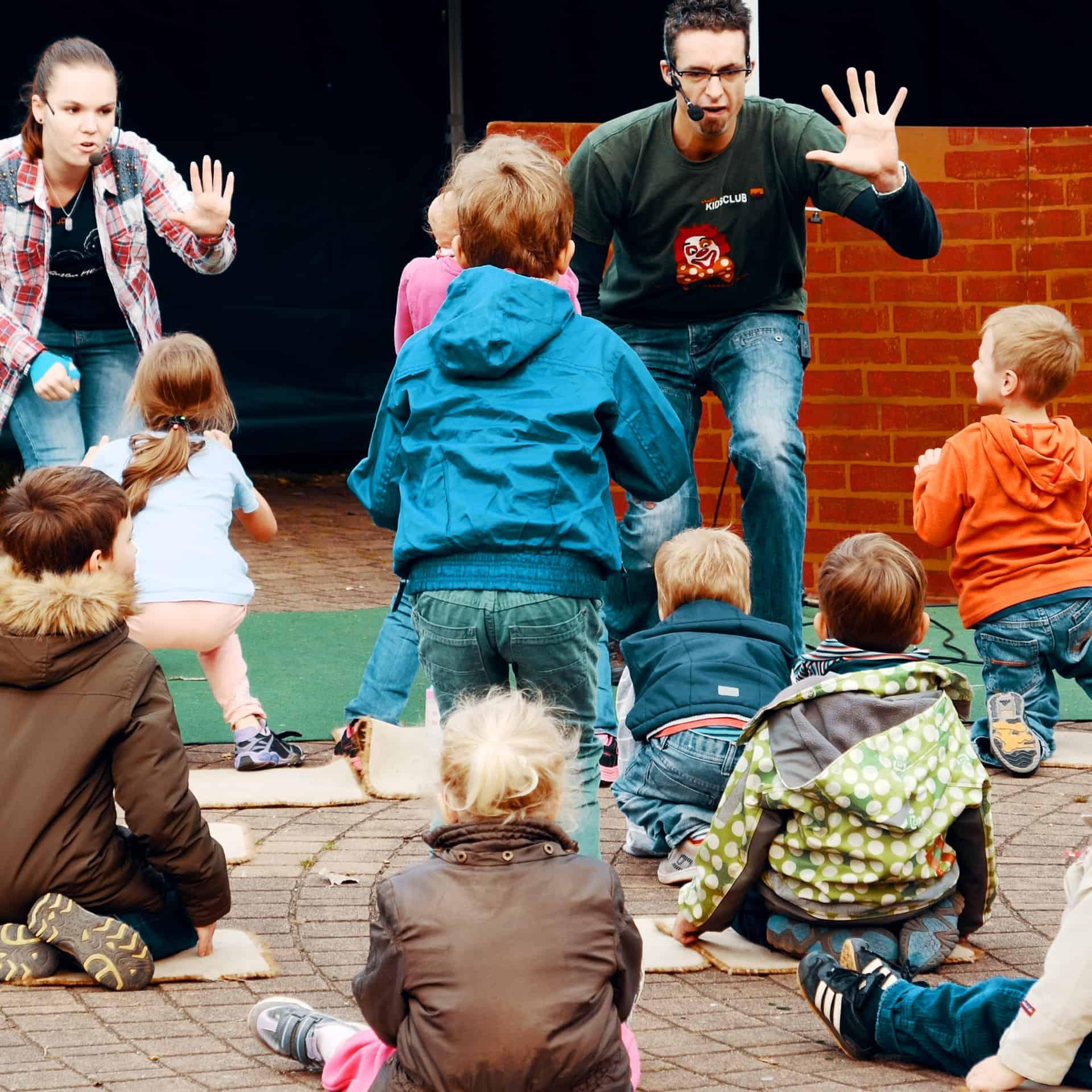 Kinder hören gespannt beim Kidsclub zu.