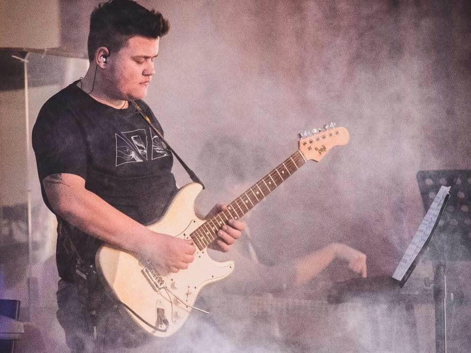 Junger Mann als Gitarrist auf Bühne
